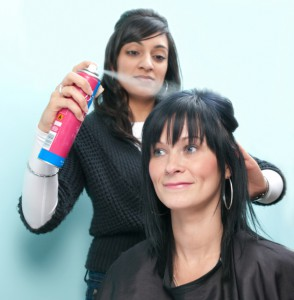 Hair stylist sprays customer's hair